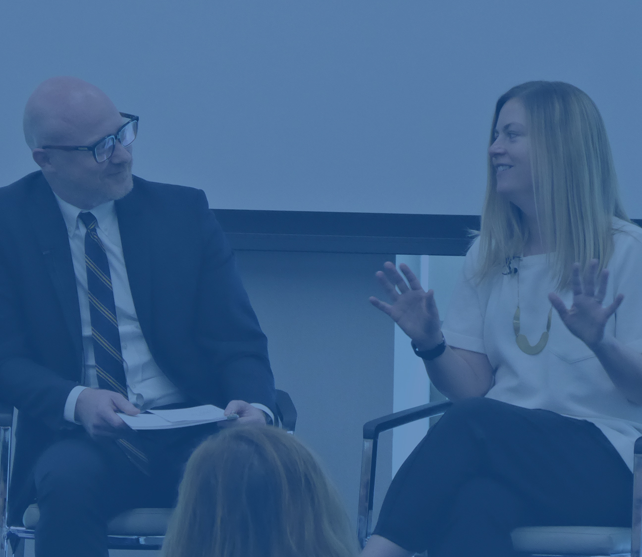 woman and man talking during a strategic communication conference panel